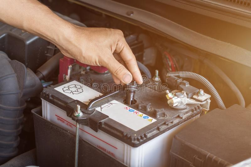 Agua y batería de trabajo del sistema del control del mecánico de automóviles llenar un motor de coche viejo en la gasolinera, el imagen de archivo libre de regalías