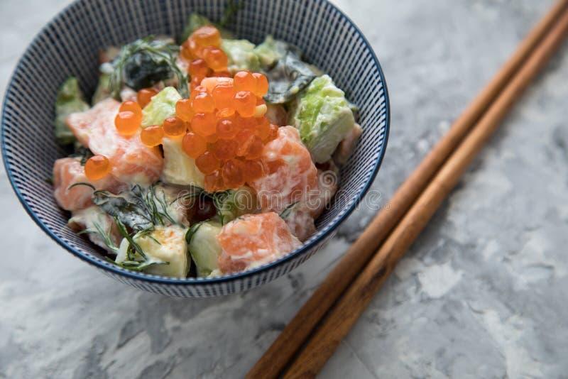 Aguacate de color salmón crudo tártaro con eneldo y el caviar de Keta en cuenco de la porcelana con los palillos de madera foto de archivo libre de regalías