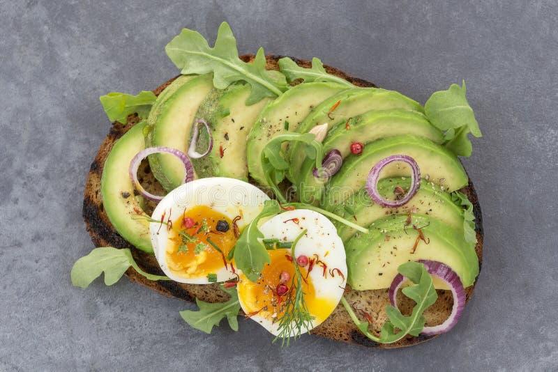 Aguacate del pan del trigo integral, bocadillo con las hierbas frescas, redonion del huevo escalfado, en fondo gris de la pizarra fotografía de archivo