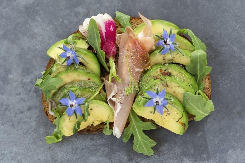 Aguacate del pan del trigo integral, bocadillo de jamón del smockef con las hierbas frescas, borraja, en fondo gris de la pizarra foto de archivo