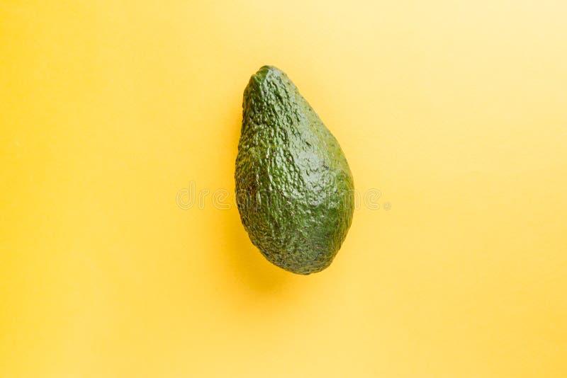 Aguacate entero verde en amarillo foto de archivo libre de regalías