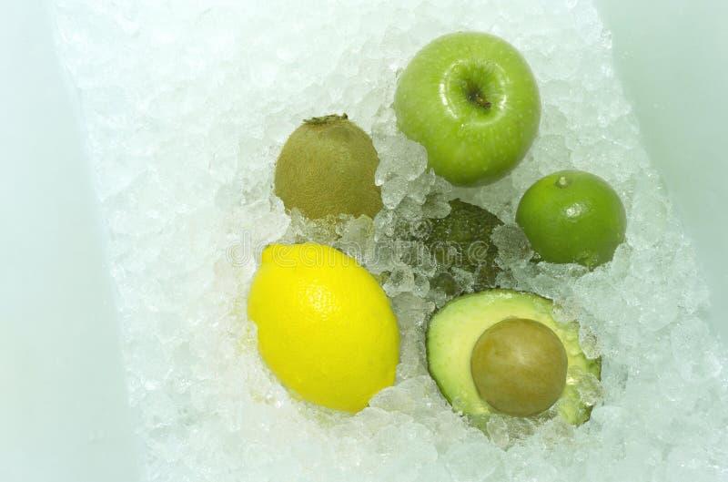 Aguacate fresco, kiwi, manzana verde, limón en fondo del hielo fotografía de archivo
