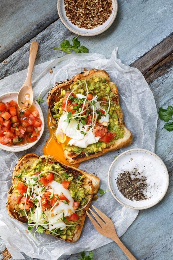 Aguacate, huevo escalfado y tostada del tomate fotos de archivo