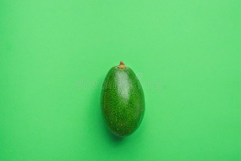 Aguacate orgánico en fondo monocromático sólido del verde de la lechuga o Endecha minimalista creativa del plano imagen de archivo