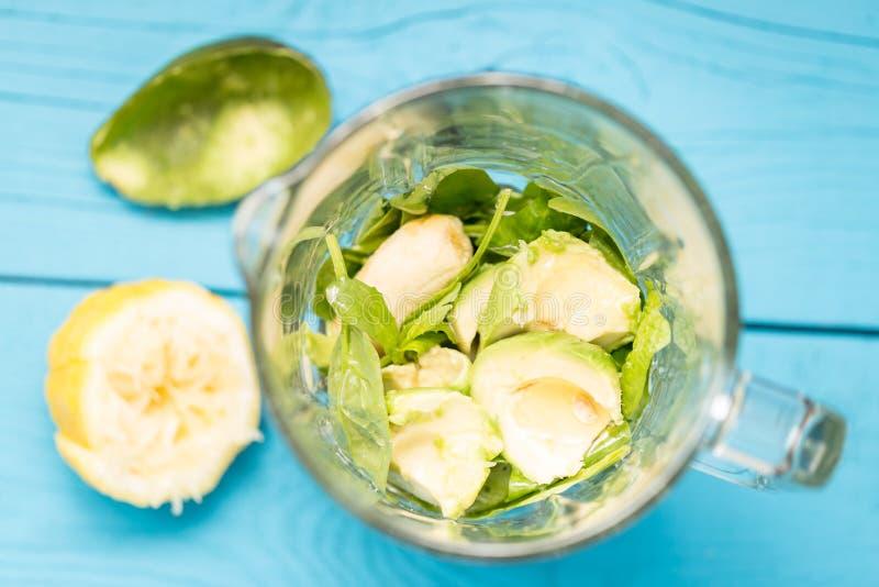 Aguacate, plátano, jugo de limón, leche de la espinaca y de la almendra en mezclador, sacudida verde sabrosa absolutamente asombr foto de archivo libre de regalías