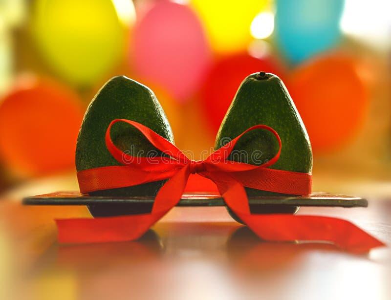 Aguacate verde con la cinta de seda roja en fondo colorido de los globos Símbolo sano del cuidado y de la relación Romance mínimo foto de archivo libre de regalías