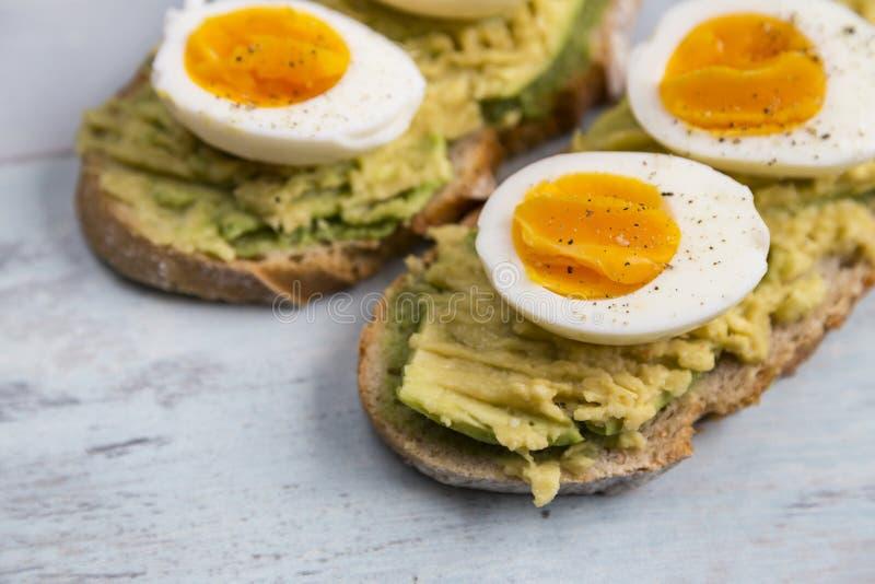 Aguacate y huevo en tostada imagenes de archivo