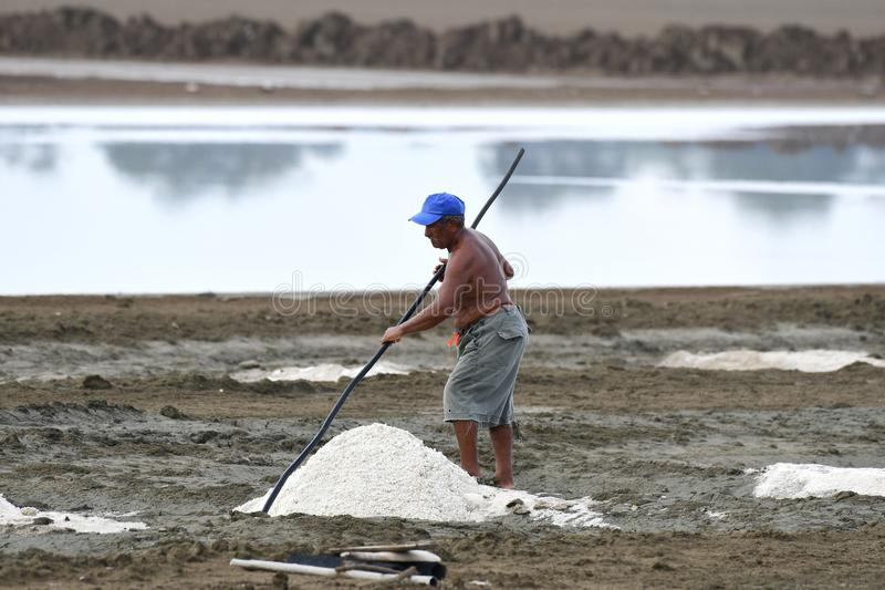 Old man harvesting salt from sea water ponds in Panama. AGUADULCE, COCLE,PANAMA-MAY 10, 2018: In addition to sugar cane, Aguadulce has the biggest salt producing stock photography