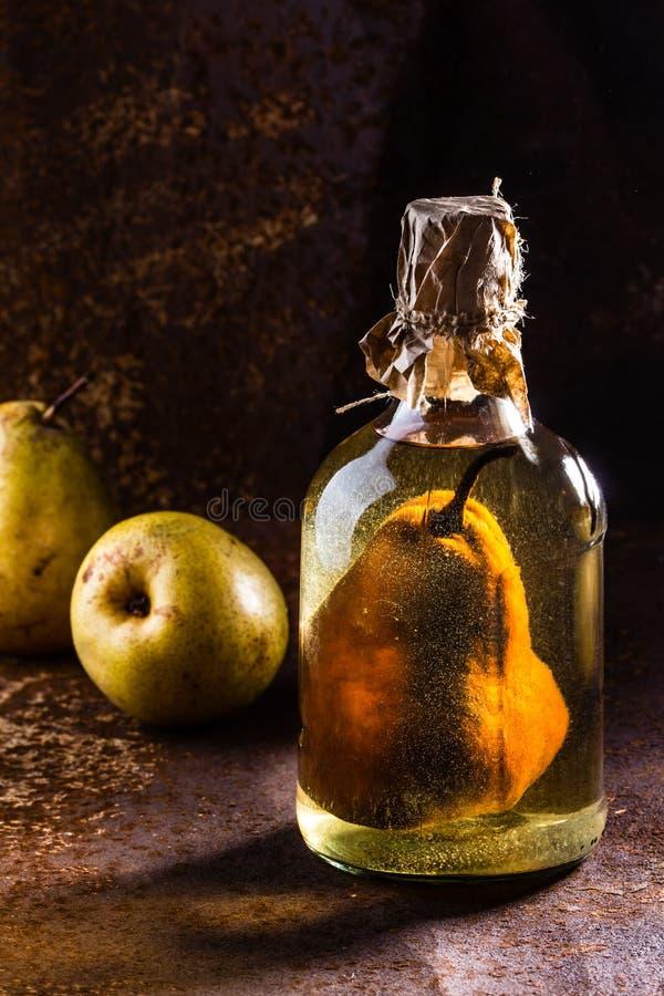 Aguardente chilena com a pera inteira dentro da garrafa Aguardiente de pera foto de stock