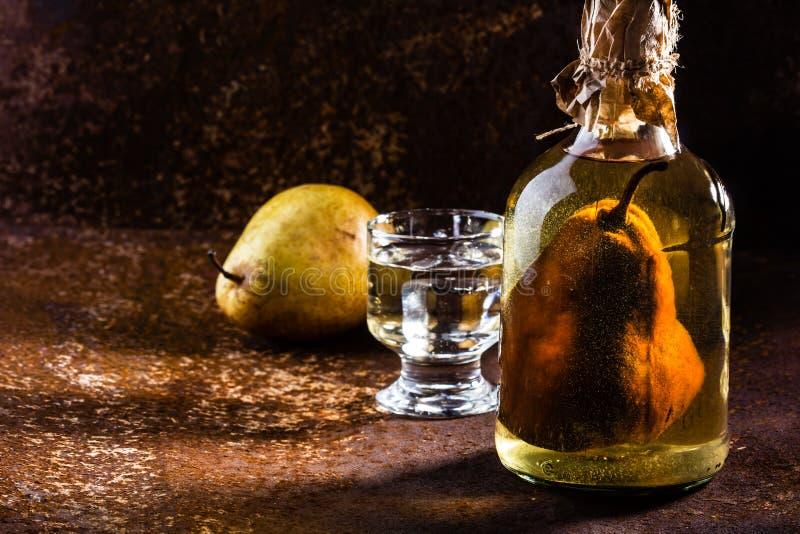 Aguardente chilena com a pera inteira dentro da garrafa Aguardiente de pera imagens de stock royalty free