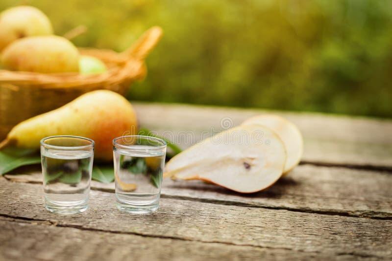 Aguardente e peras da pera na tabela fotografia de stock
