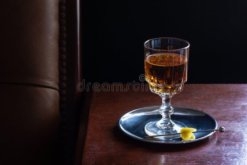Aguardente, uísque, ou licor de Brown no vidro na barra escura imagens de stock