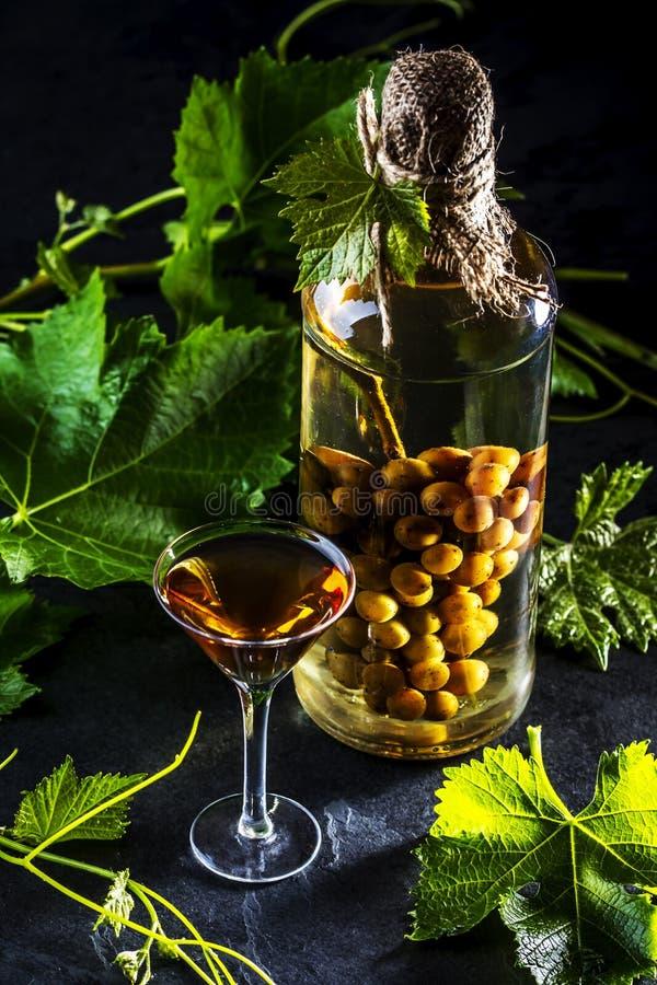 Aguardiente chileno da aguardente com grupo de uvas inteiro dentro da garrafa imagem de stock royalty free