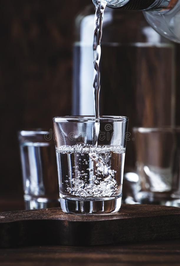 Aguardiente - traditional Spanish strong alcoholic drink, grape moonshine or vodka, in glasses on an old wooden table, place for. Text stock photo