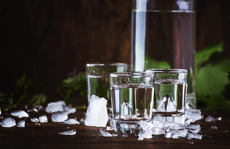 Aguardiente - traditional Spanish strong alcoholic drink, grape moonshine or vodka, in glasses on an old wooden table, place for. Text royalty free stock images