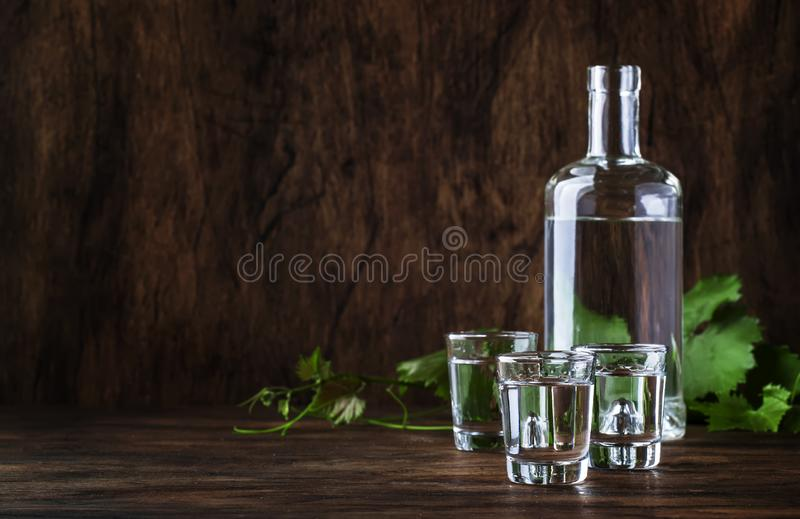 Aguardiente - traditional Spanish strong alcoholic drink, grape moonshine or vodka, in glasses on an old wooden table, place for. Text royalty free stock photo