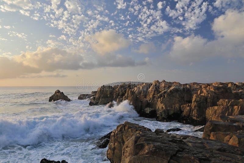 Aguas que hacen espuma en la puesta del sol en una playa imagen de archivo