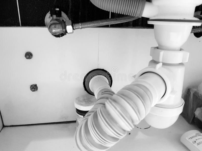 Aguas residuales con el tubo y el sifón acanalados en el cuarto de baño imagen de archivo