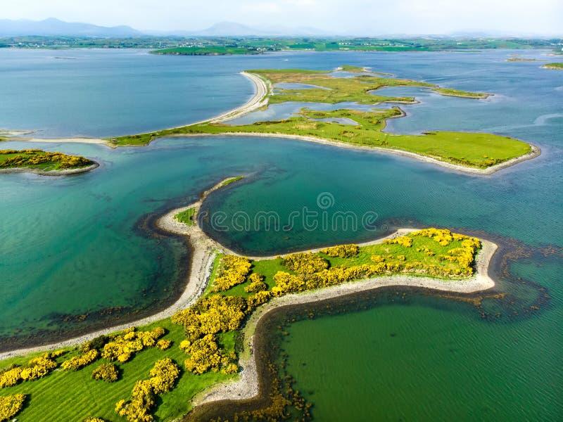 Aguas verdes esmeralda vivas y pequeñas islas cerca de la ciudad a lo largo de la manera atlántica salvaje, Irlanda de Westport foto de archivo libre de regalías