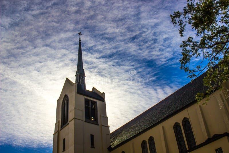 Aguja de la iglesia enmarcada contra el cielo nublado imagenes de archivo