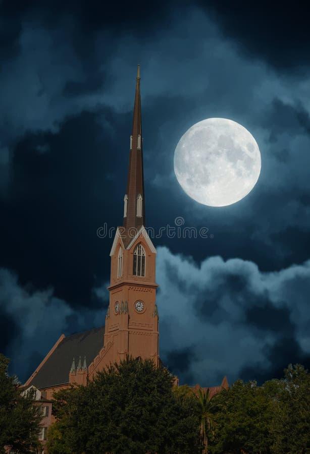 Aguja roja del estuco que sube en noche iluminada por la luna foto de archivo