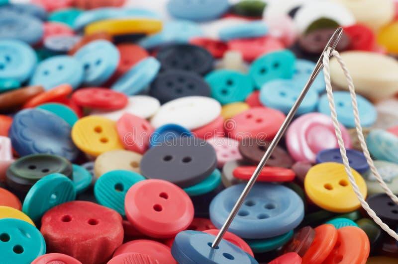Aguja y botones foto de archivo