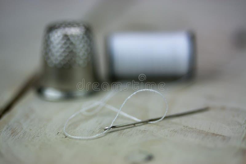 Aguja y dedal de costura del algodón fotografía de archivo