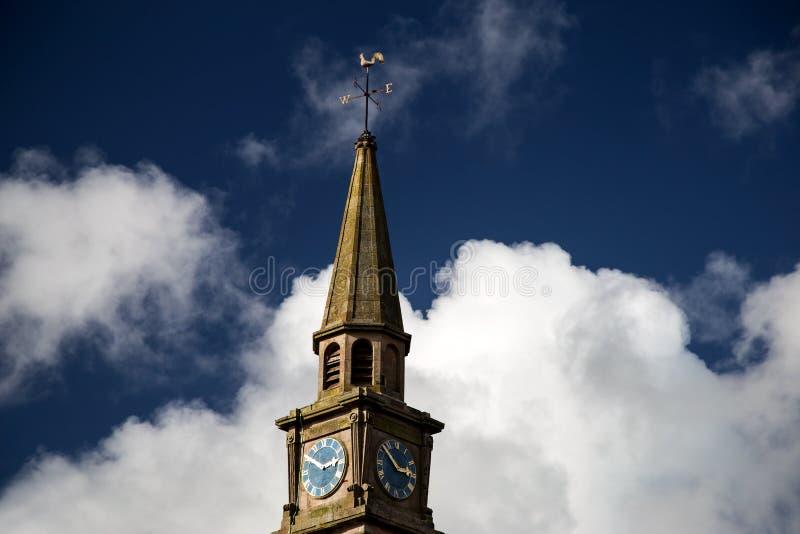 Aguja y reloj de la iglesia contra un cielo nublado azul foto de archivo