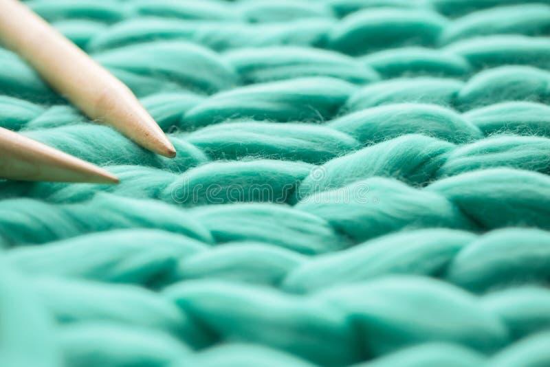 agujas que hacen punto de madera en el fondo de la manta de la lana merina foto de archivo libre de regalías