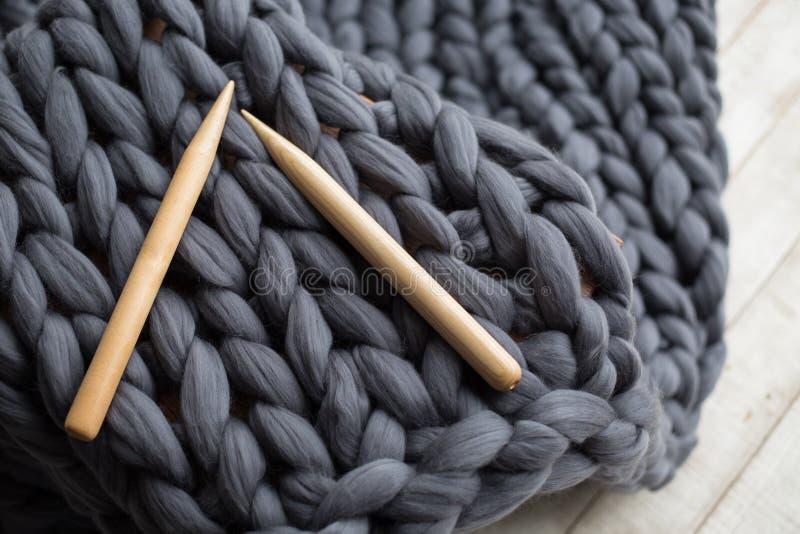 Agujas que hacen punto de madera en fondo de la lana merina gris imagenes de archivo