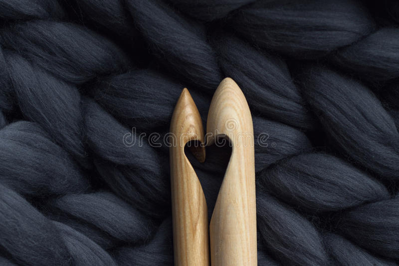 Agujas que hacen punto de madera en fondo del blanke gris de la lana merina imagenes de archivo