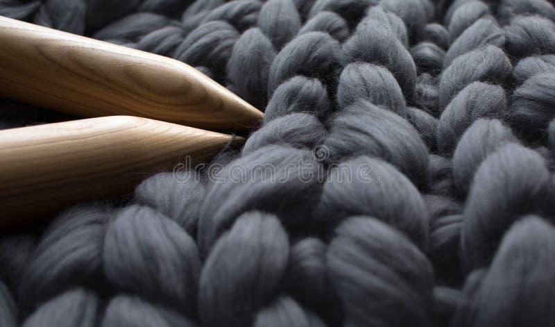 Agujas que hacen punto de madera en fondo del blanke gris de la lana merina imagen de archivo