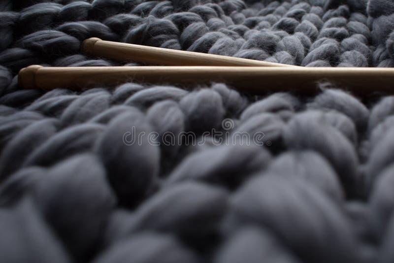 Agujas que hacen punto de madera en fondo del blanke gris de la lana merina foto de archivo