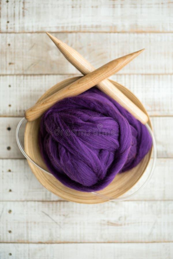 Agujas que hacen punto de madera y bola púrpura de la lana merina en una cesta foto de archivo libre de regalías