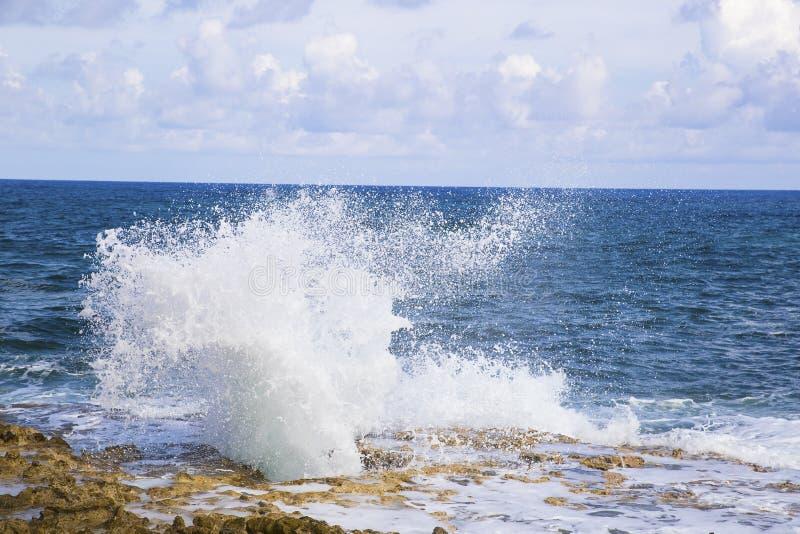 Agujero bonito del soplo en la isla de Grand Cayman con el espray de mar fotografía de archivo