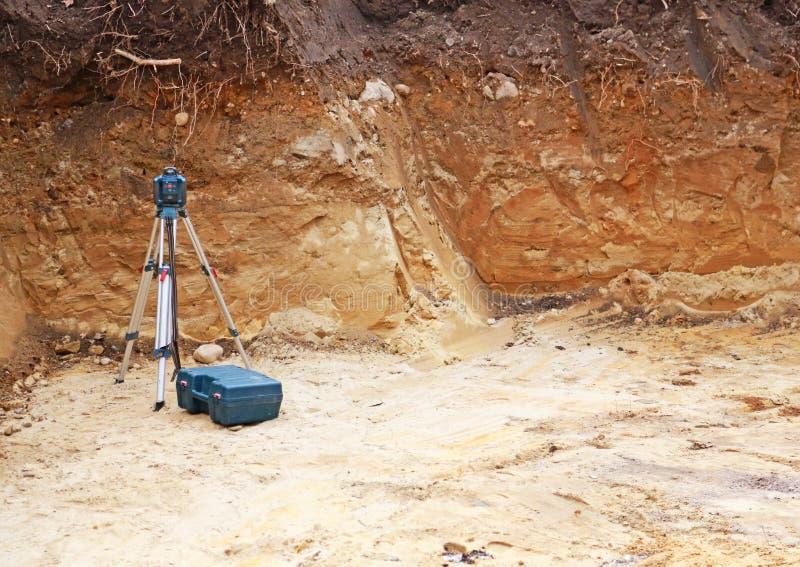 Agujero con la explotación minera o equipo del topógrafo con área de texto imagen de archivo libre de regalías