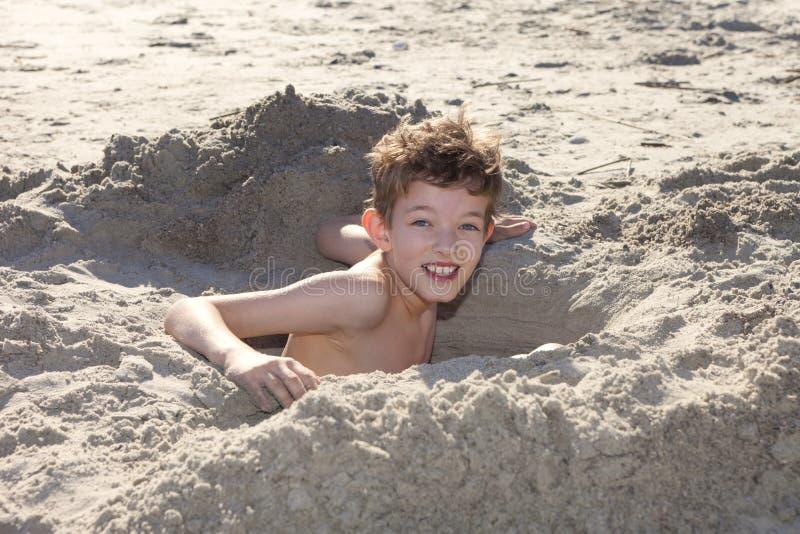 Agujero de excavación del muchacho en arena fotos de archivo libres de regalías