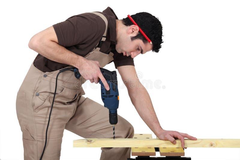 Agujero de perforación del hombre en madera imagenes de archivo