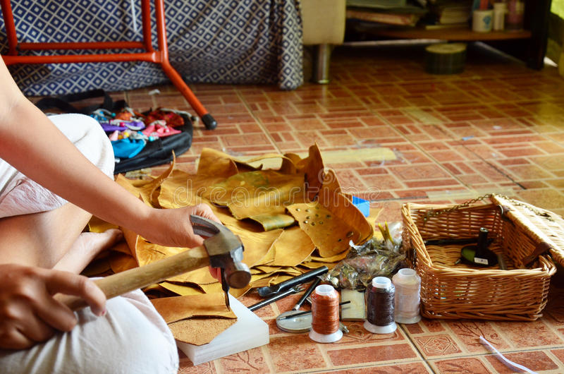 Agujero de perforación tailandés de la mujer en el cuero para el cuero hecho a mano hecho del bolso fotografía de archivo libre de regalías