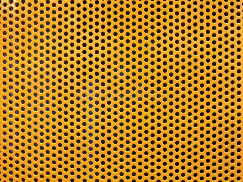 Agujero del metal amarillo o fondo perforado de la rejilla imagenes de archivo