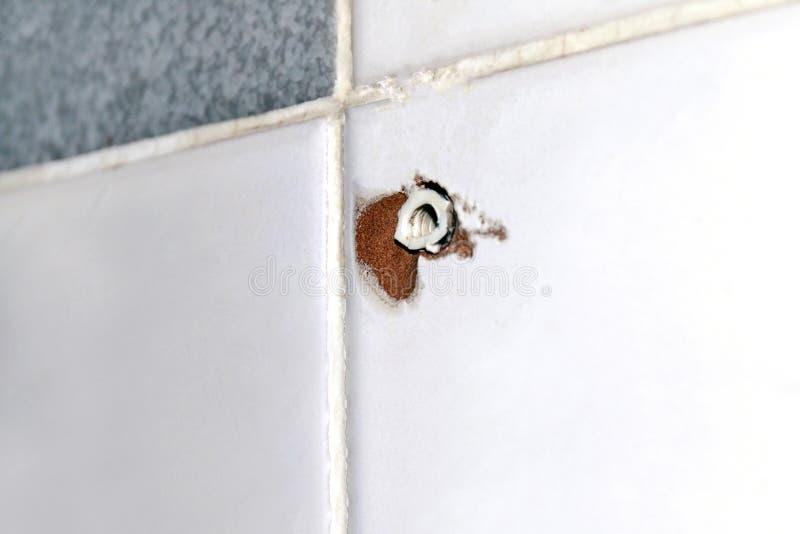 Agujero del perno de extensión viejo en la pared de la teja, anclas plásticas viejas para los tornillos de los pasadores, tornill imágenes de archivo libres de regalías