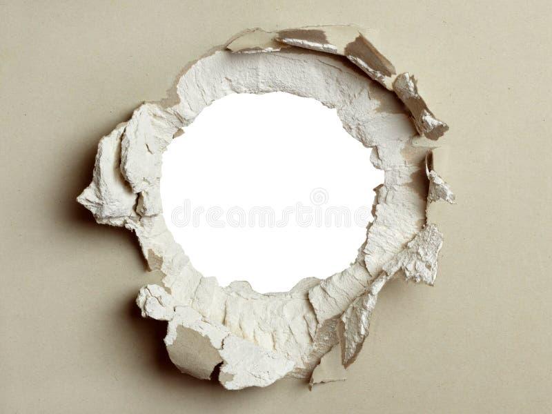 Agujero en el cartón yeso gris. foto de archivo