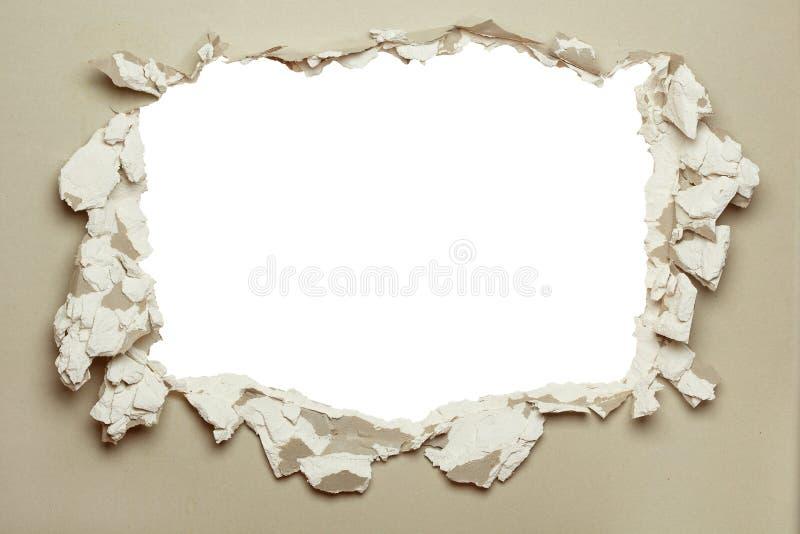 Agujero en el cartón yeso gris. fotos de archivo