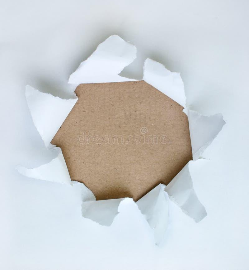 Agujero en el papel con las caras rasgadas fotos de archivo