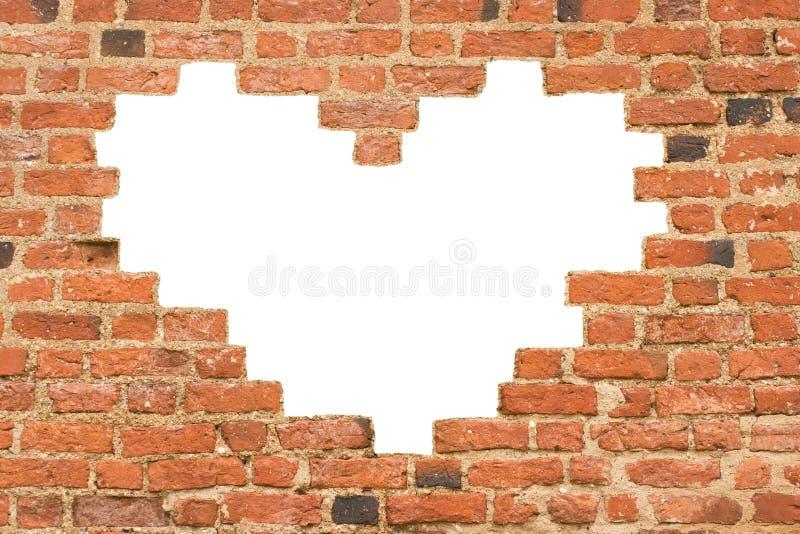 Agujero en forma de corazón en pared de ladrillo imagen de archivo libre de regalías