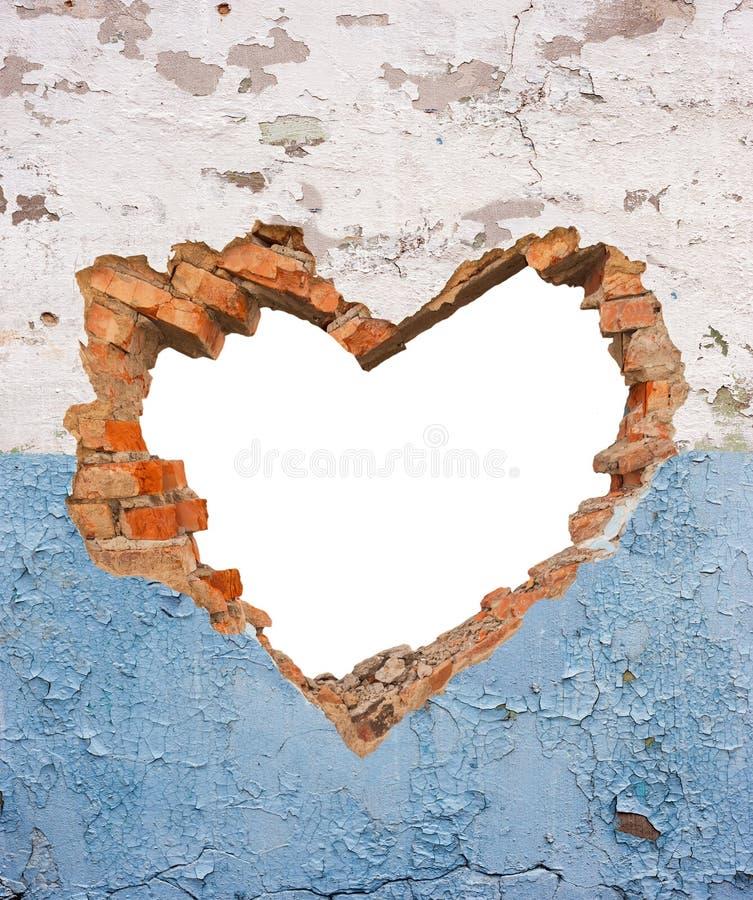 Agujero en forma de corazón en pared de ladrillo vieja fotos de archivo