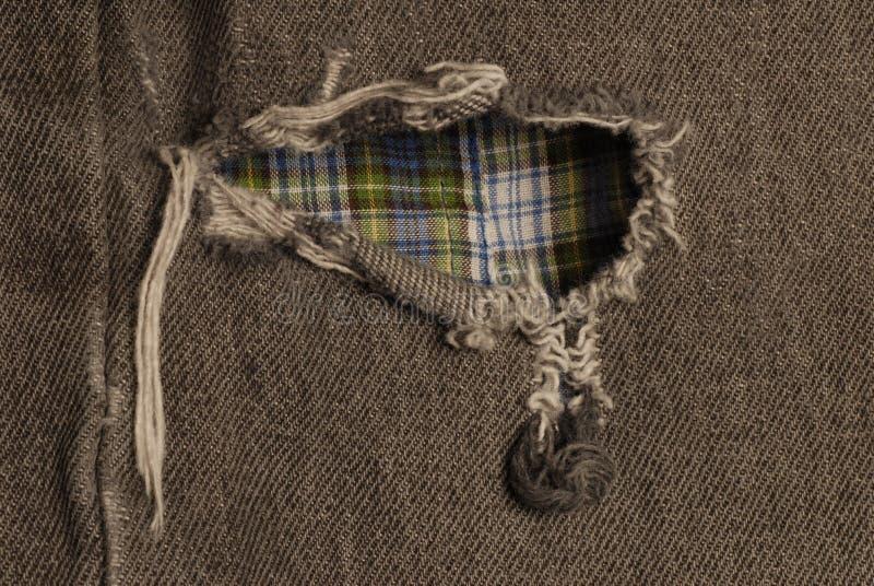 Agujero en pantalones vaqueros gastados imagen de archivo