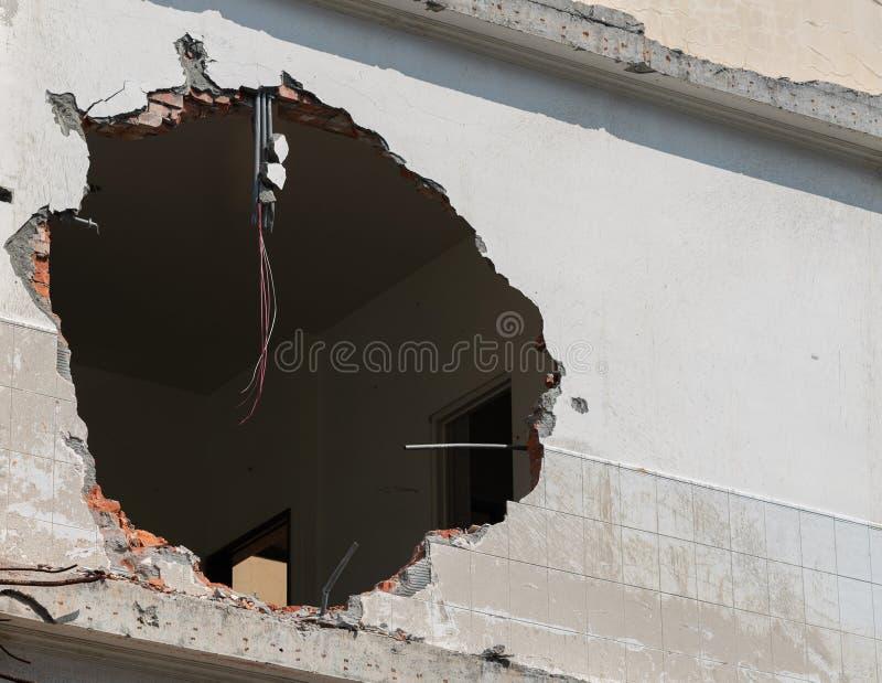 Agujero enorme con los alambres que cuelgan en pared del edificio y espacio de la copia fotos de archivo