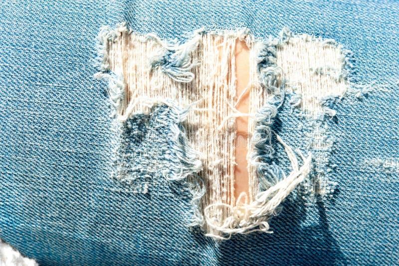 Agujero rasgado en textura azul del dril de algodón Al aire libre primer imagenes de archivo
