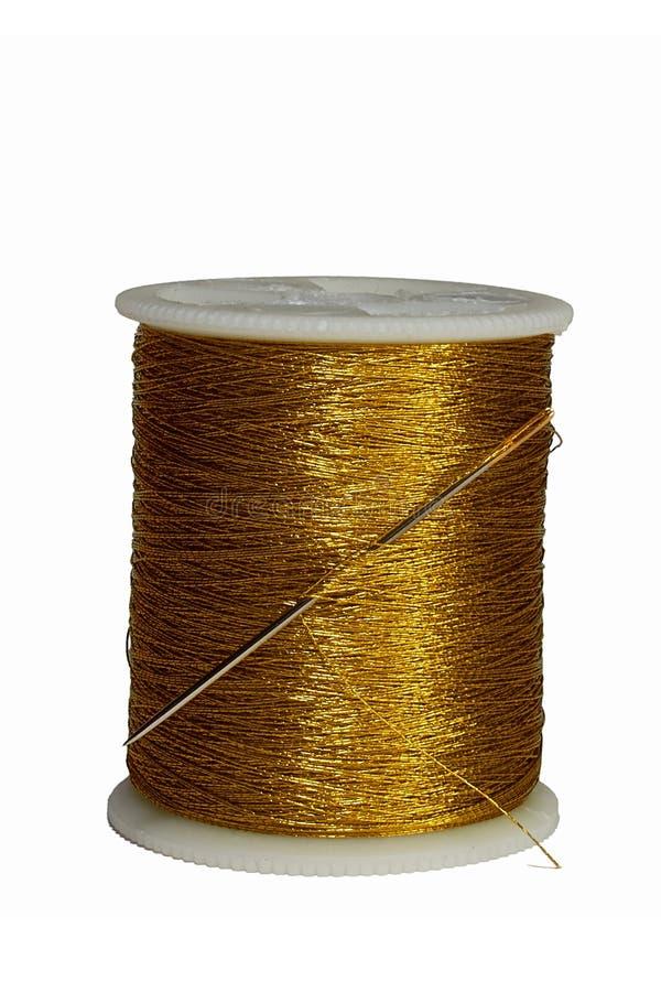 Agulha colada na linha do ouro do carretel isolada no fundo branco fotos de stock royalty free